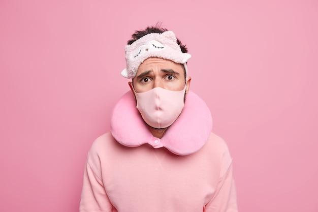 Mężczyzna nosi maskę do spania wygodną poduszkę pod szyję maska ochronna na twarz jadący transportem publicznym podczas rozprzestrzeniania się koronawirusa ma zmartwiony wyraz twarzy