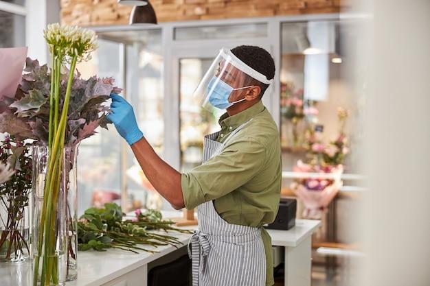 Mężczyzna nosi maskę ochronną i robi bukiety świeżych kwiatów w kwiaciarni