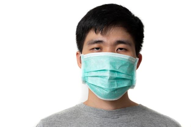 Mężczyzna nosi oddychającą medyczną maskę oddechową przeciwko koronawirusowi (covid-19) na białym tle.