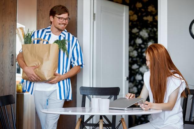 Mężczyzna nosi paczkę z produktami, gdy kobieta pracuje w domu