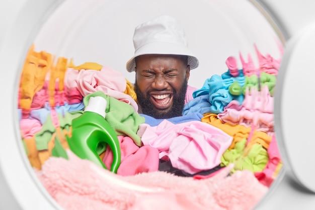 Mężczyzna nosi panama pozuje obok stosu kolorowych detergentów do prania sfotografowany z wnętrza pralki śmieje się radośnie