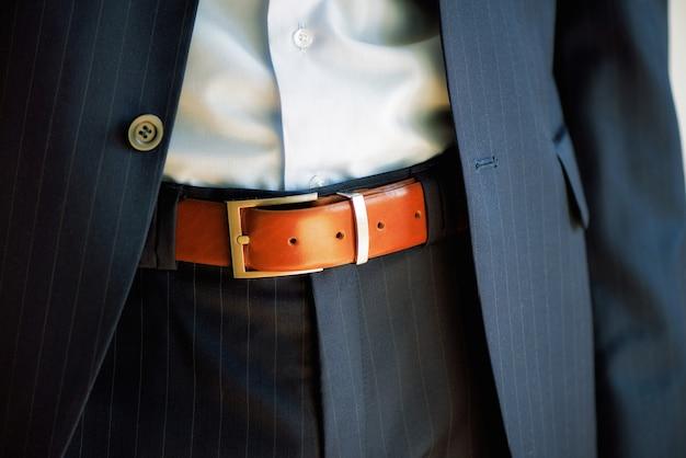 Mężczyzna nosi pas. młody biznesmen w przypadkowym garniturze z akcesoriami. koncepcja mody i odzieży. przygotowuje się rano przed ceremonią