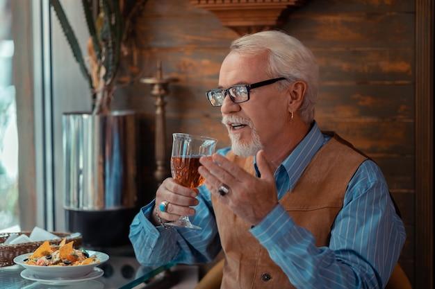 Mężczyzna nosi pierścień. brodaty starszy mężczyzna noszący pierścionek i kolczyk pijący alkohol