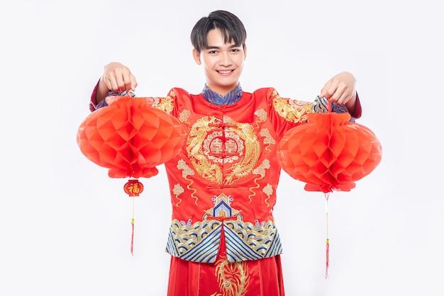 Mężczyzna nosi pokaz garnituru cheongsam udekoruje czerwoną lampę do swojego sklepu w chiński nowy rok