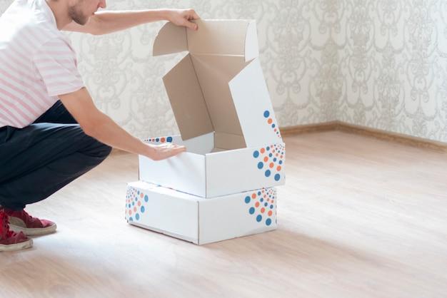 Mężczyzna nosi pudełka z kreskówkami i przenosi się do nowej koncepcji mieszkania domowego