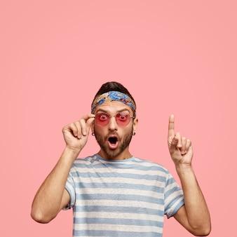 Mężczyzna nosi różowe okulary i kolorową chustkę