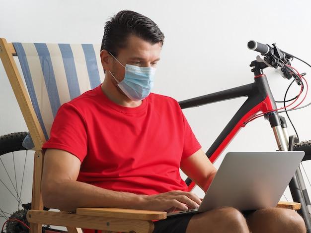 Mężczyzna nosić medyczną maskę na twarz, chronić przed infekcją wirusem, pandemią, wybuchem i epidemią pracy koronawirusa na laptopie w domu.