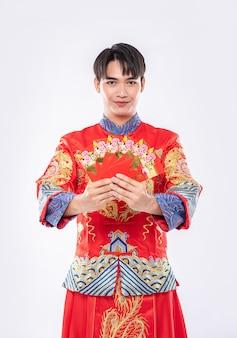 Mężczyzna noszący cheongsam ma szczęście, że w tradycyjny dzień otrzymuje od rodziców pieniądze w prezencie