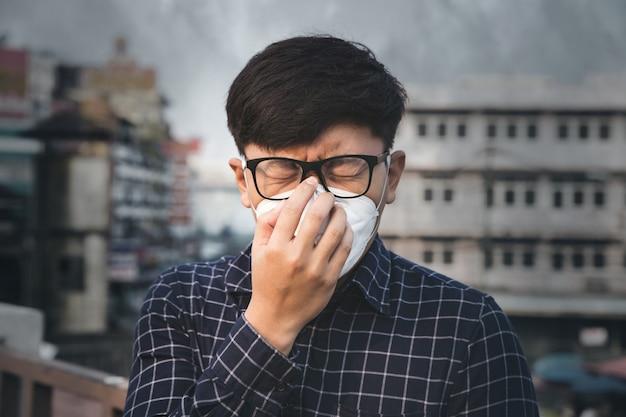 Mężczyzna noszący maskę ochronną dróg oddechowych przed zanieczyszczeniem powietrza i cząsteczkami pyłu przekracza normy bezpieczeństwa. pojęcie opieki zdrowotnej, środowiska, ekologii.