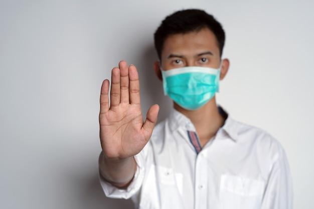 Mężczyzna noszący maskę zdrowotną z gestem zatrzymania przed kamerą na białym tle