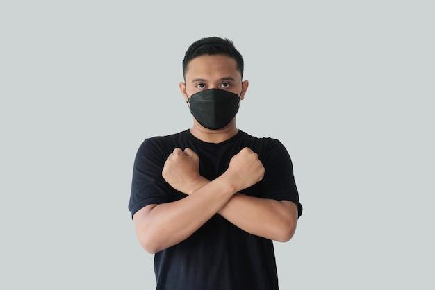 Mężczyzna noszący maskę ze skrzyżowanymi rękami