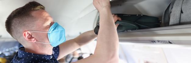 Mężczyzna noszący ochronną maskę medyczną, kładący swój bagaż podręczny na półce samolotu