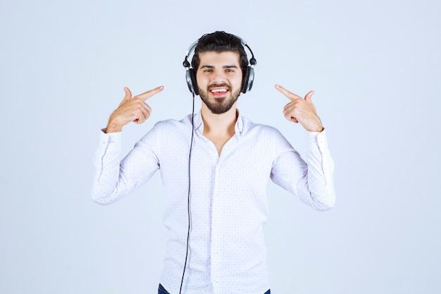 Mężczyzna noszący słuchawki i cieszący się muzyką