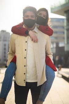 Mężczyzna noszący swoją dziewczynę na ramionach i noszący maski chroniące przed pandemią koronawirusa covid 19