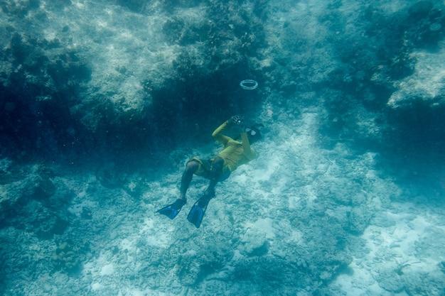 Mężczyzna nurkuje w bańkę w niebieskim oceanie