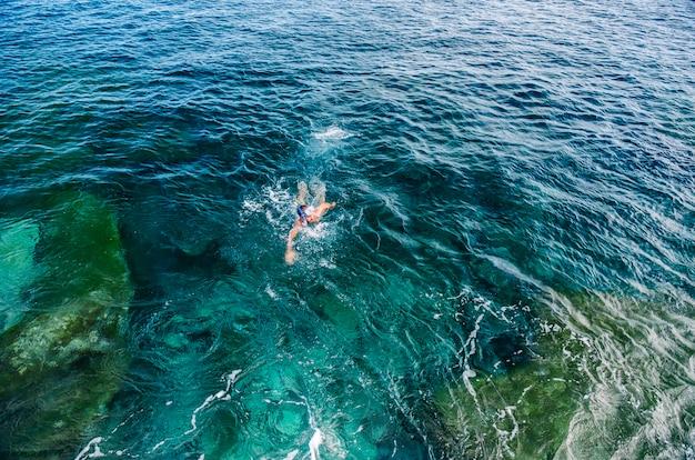 Mężczyzna nurkuje w okularach i tubie i kąpie się w morzu w turkusowo-niebieskim kolorze