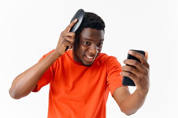 Mężczyzna o afrykańskim wyglądzie przeczesujący głowę z telefonem w dłoniach