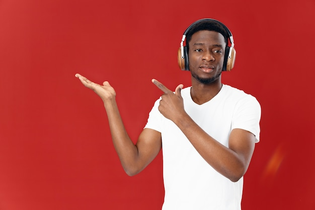 Mężczyzna o afrykańskim wyglądzie w białej koszulce ze słuchawkami słuchającymi technologii muzycznej