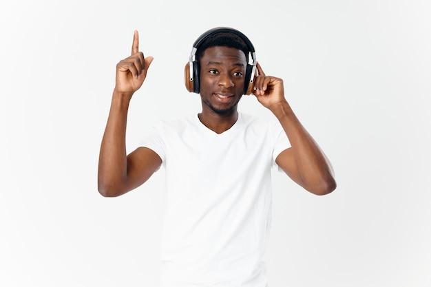 Mężczyzna o afrykańskim wyglądzie w słuchawkach słuchający muzyki biała koszulka na białym tle