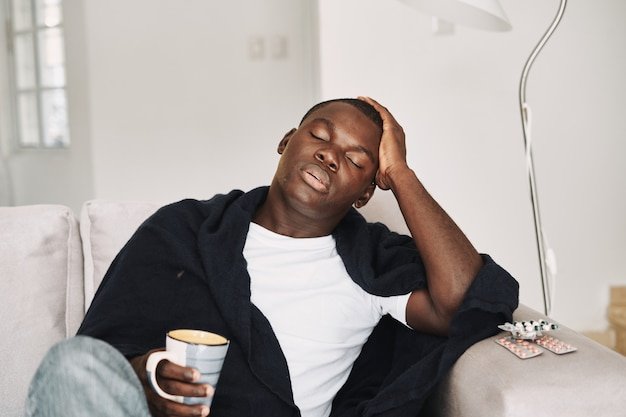Mężczyzna o afrykańskim wyglądzie z filiżanką kawy w dłoni