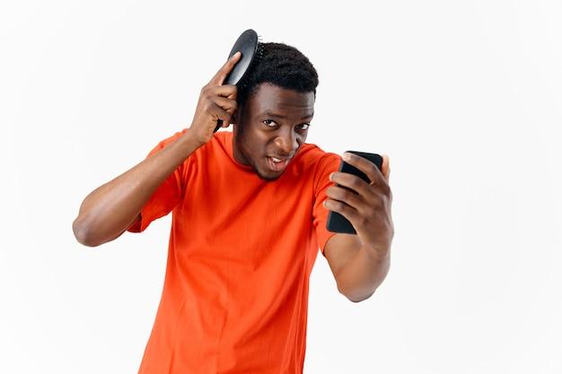 Mężczyzna o afrykańskim wyglądzie z telefonem w dłoniach czeszący fryzurę na głowie