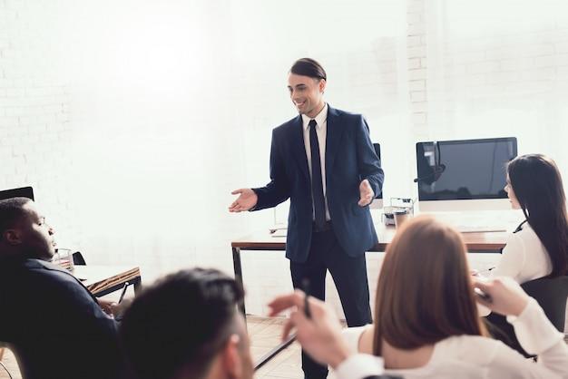 Mężczyzna o arabskim wyglądzie wygłasza wykład dla pracowników biurowych