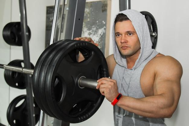 Mężczyzna o dużych mięśniach zajmuje się podnoszeniem ciężarów na siłowni. nakręcony sportowiec uprawia sport na symulatorach wagi ciężkiej. ćwiczenia sportowe.