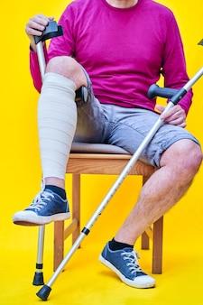 Mężczyzna o kulach, dżinsach i fioletowej koszuli siedzi na krześle, podpierając obandażowaną nogę o kulę.