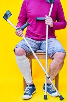 Mężczyzna o kulach, dżinsach i fioletowej koszuli siedzi na krześle z zabandażowaną nogą.