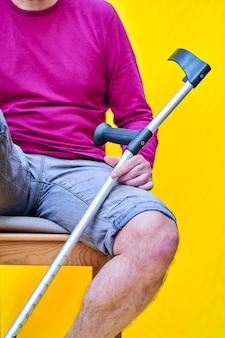 Mężczyzna o kulach, dżinsach i fioletowej koszuli siedzi na krześle.