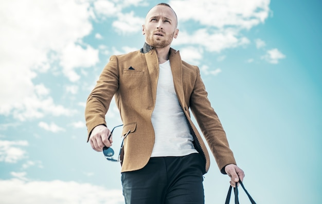 Mężczyzna o pewnej siebie twarzy i brutalnym stylu. reklama sklepu odzieżowego. stojąc na czystym błękicie