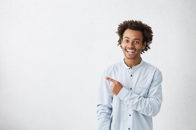 Mężczyzna o specyficznym wyglądzie ubrany formalnie, wskazując na białą pustą ścianę
