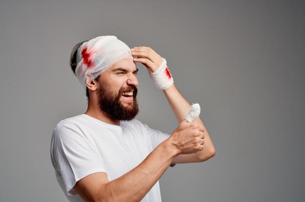 Mężczyzna obandażowana głowa i ręka krwi na białym tle