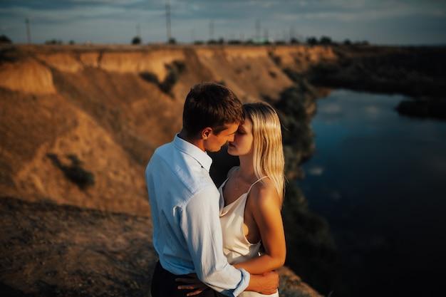 Mężczyzna obejmując i całując zmysłową kobietę w dniu ślubu.