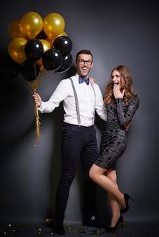 Mężczyzna obejmując i dając bukiet balonów swoją zaskoczoną dziewczyną