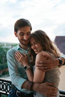 Mężczyzna obejmując żonę na balkonie. zrelaksowana para cieszy się dniem i dobrymi wiadomościami. szczęśliwa młoda rodzina