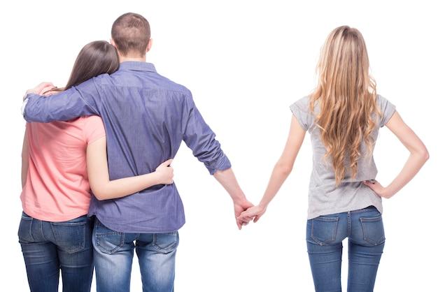 Mężczyzna obejmuje swoją dziewczynę, trzymając się za ręce innej dziewczyny.