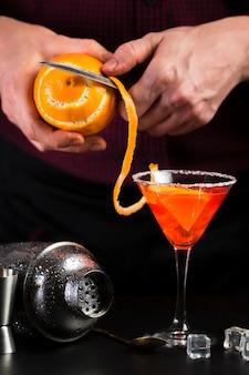 Mężczyzna obierania pomarańcze dla koktajlu