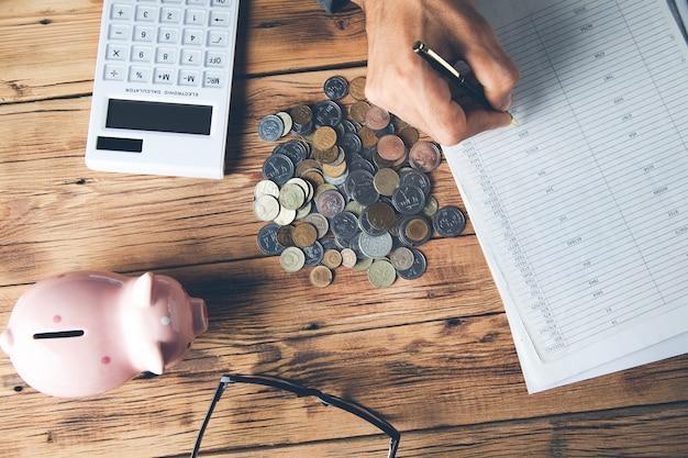 Mężczyzna oblicza pieniądze skarbonka i dokumenty biznesowe na biurku