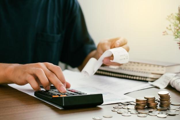Mężczyzna oblicza rachunki domowe w domu mężczyzna za pomocą kalkulatora sprawdzającego saldo i koszty w biurze