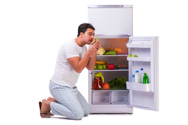 Mężczyzna obok lodówki pełnej jedzenia