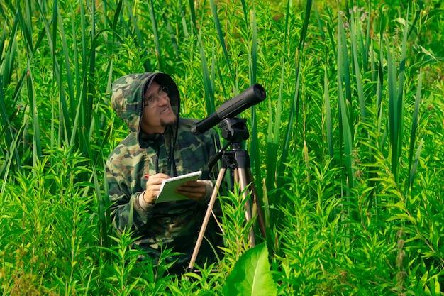 Mężczyzna obserwator ptaków rejestruje wyniki obserwacji na mokradłach