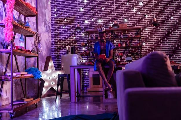 Mężczyzna obserwujący bałagan. ciemnowłosy facet w jedwabnej kobiecej piżamie i siedzący na stole obserwujący informacje w tablecie