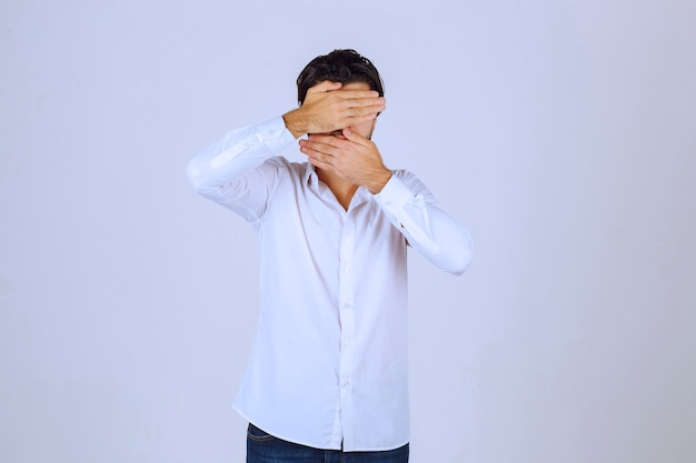 Mężczyzna obserwujący na zewnątrz palcami lub chowający twarz.