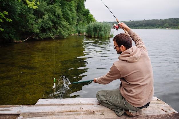 Mężczyzna obsiadanie na mola łapania ryba z połowem prącie