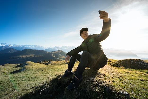 Mężczyzna obsiadanie na skale i selfie w trevel