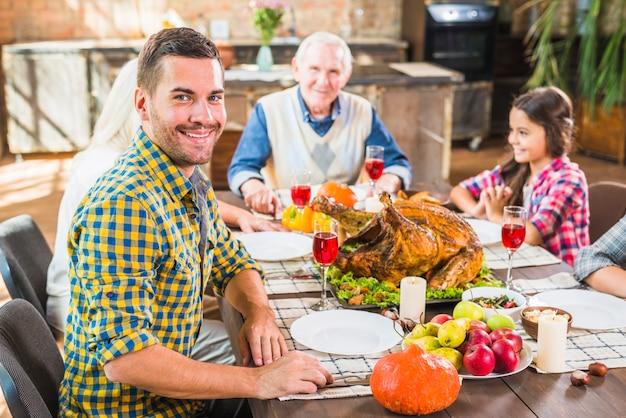 Mężczyzna obsiadanie przy stołową pobliską rodziną
