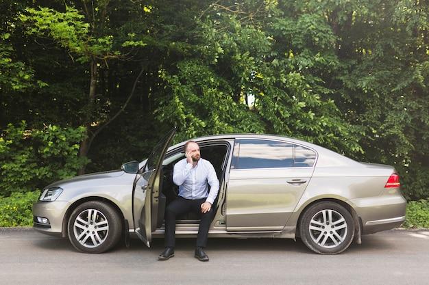 Mężczyzna obsiadanie w samochodzie z otwarte drzwi bierze na telefonie komórkowym