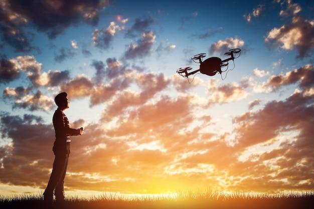 Mężczyzna obsługujący drona o zachodzie słońca za pomocą kontrolera. renderowanie 3d