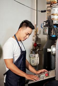 Mężczyzna obsługujący maszynę do palenia kawy